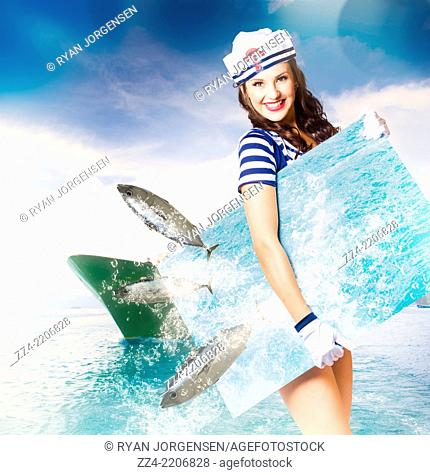 Creative portrait of a gorgeous young navy pin up model having fun while holding a tropical sea board with fish jumping through