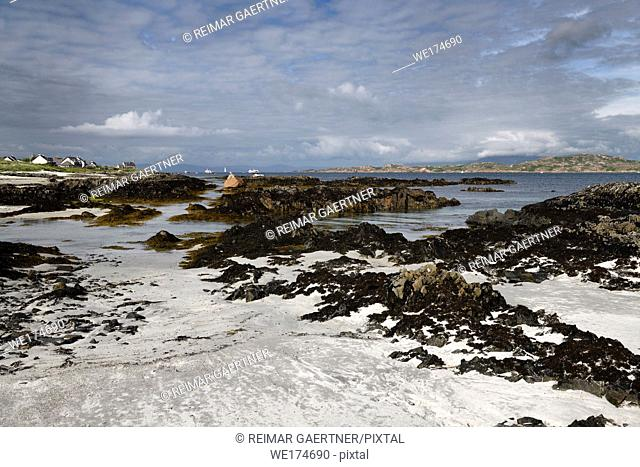 White sand and rocks on the shore of Isle of Iona with Isle of Mull on other side of Sound of Iona Inner Hebrides Scotland UK