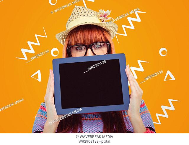 Woman in straw hat with tablet over face against orange background with white patterns