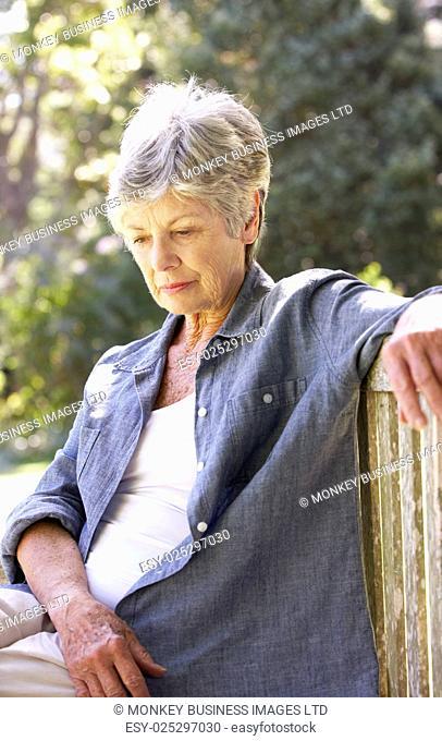 Unhappy Senior Woman Sitting On Park Bench