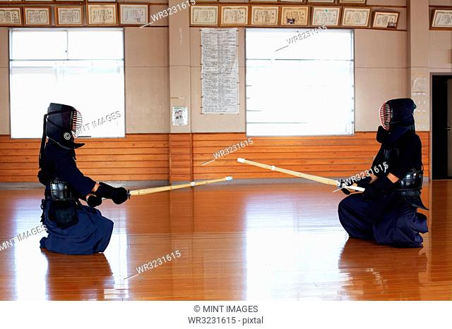 Two Japanese Kendo fighters sitting opposite each other on wooden floor, wearing Kendo masks and holding wood swords