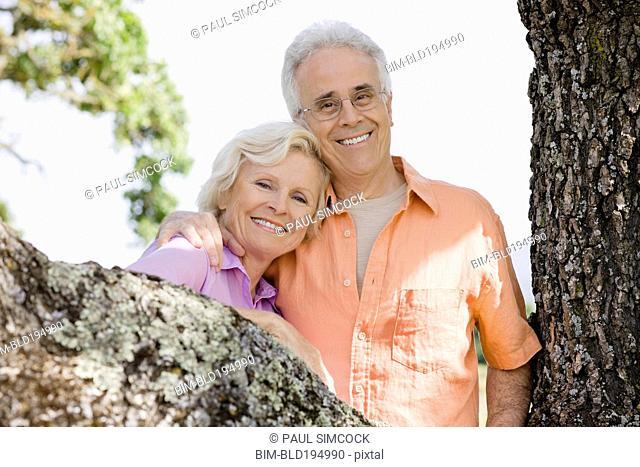 Caucasian couple posing near tree