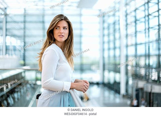 Young woman standing at railing looking around