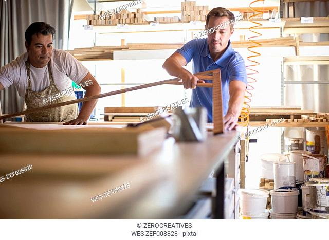 Two men working together in canvas workshop