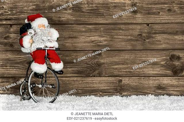 Wooden christmas background with santa on a bike. Funny greeting card for xmas