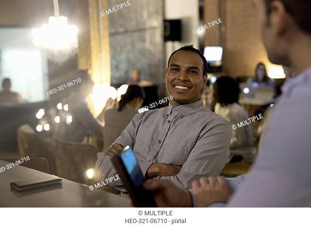 Smiling businessmen talking and using digital tablet in office
