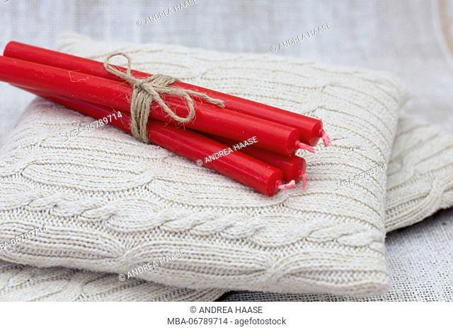 Christmas candles on cushion, still life