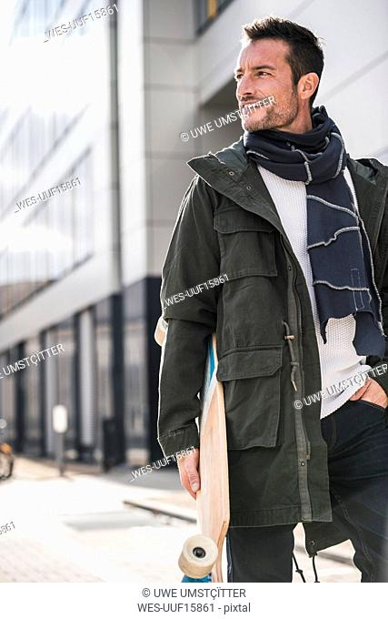Mature man, wearing coat and scarf, walking in the city, carrying longboard