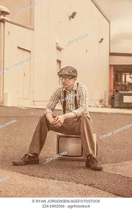 Old style image of a man sitting a retro television set sitting in the streets of old. Television is broken