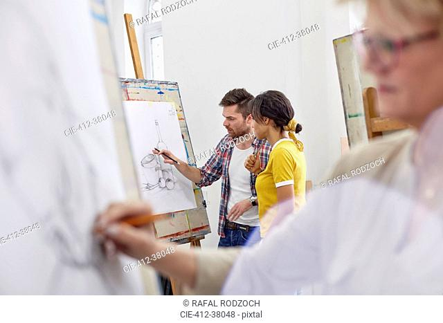 Artists discussing sketch at easel in art class studio