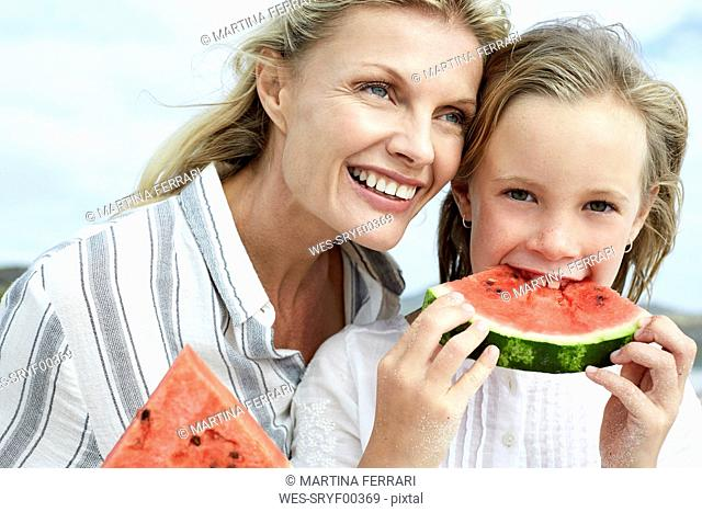 Mother and daughter eating water melon on the beach