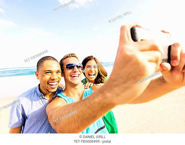 Young people taking selfie on beach