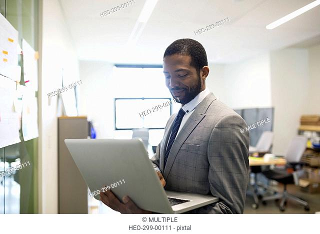 Businessman standing with laptop in office