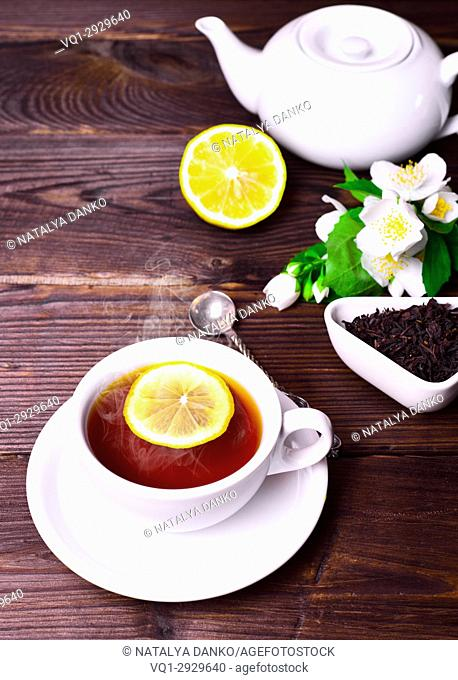 black tea in a white mug with a saucer, behind a tea pot and dry tea in a bowl on a brown wooden background