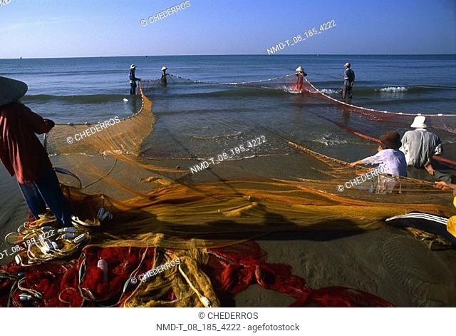 Rear view of fishermen pulling fishing nets from the sea, Vietnam