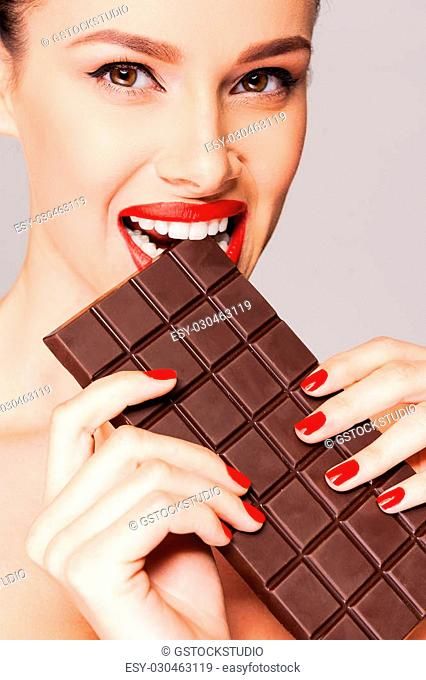 Always choosing chocolate. Close-up of a beautiful women holding finger on her red lips while standing against grey background