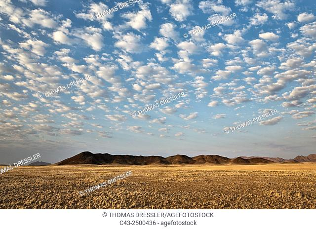 Arid plains and isolated mountain ridges at the edge of the Namib Desert. In the evening with fluffy clouds. Kulala Wilderness Reserve, Namibia