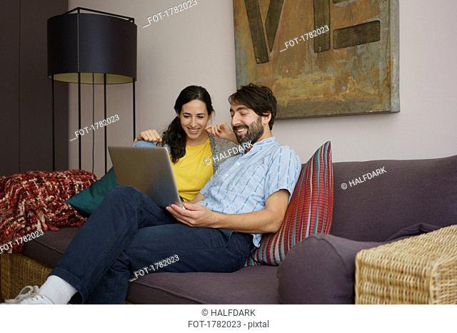 Couple using laptop on living room sofa