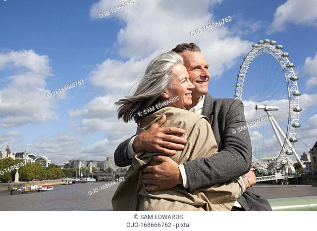 Portrait of smiling couple hugging in front of Thames river