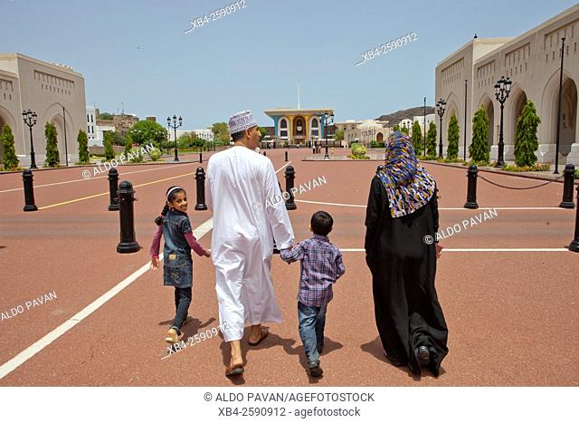 Family walking in front at the Sultan palace, Muscat, Oman