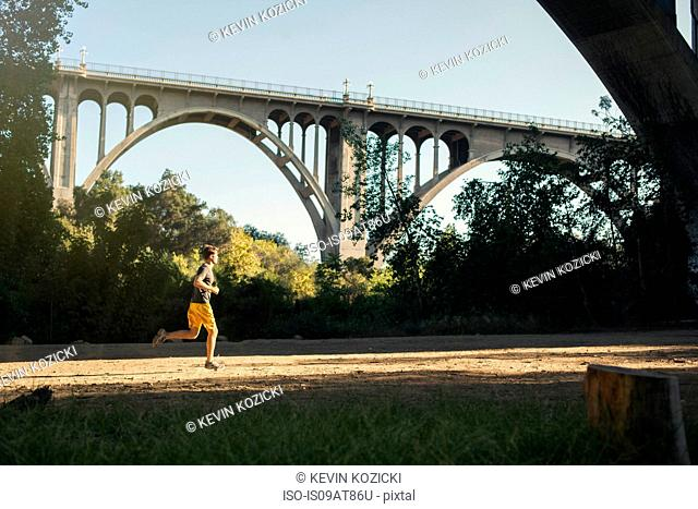 Jogger running, arch bridge in background, Arroyo Seco Park, Pasadena, California, USA