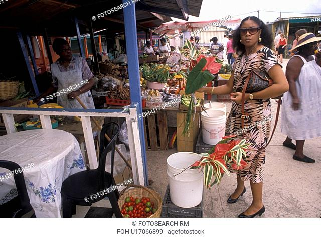 Caribbean, street market, St. Martin, Marigot, Caribbean Islands, Local woman buying flowers at a street market in Marigot the French capital of the island of...