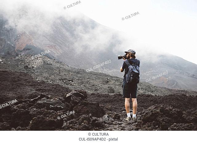 Young man photographing the Pacaya volcano, Antigua, Guatemala