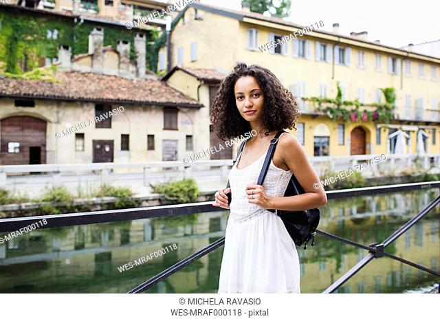 Italy, Milan, portrait of young woman with backpack wearing white summer dress