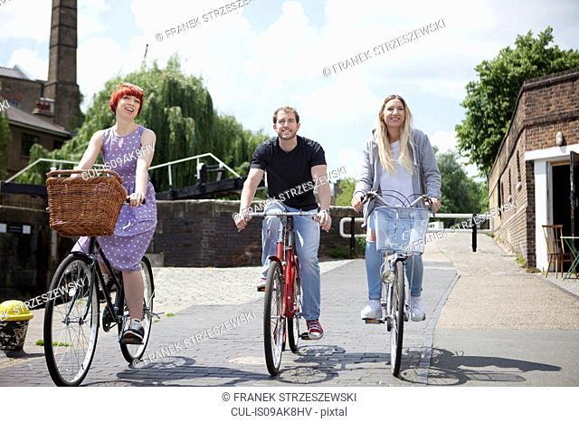 Friends riding bike along canal, East London, UK