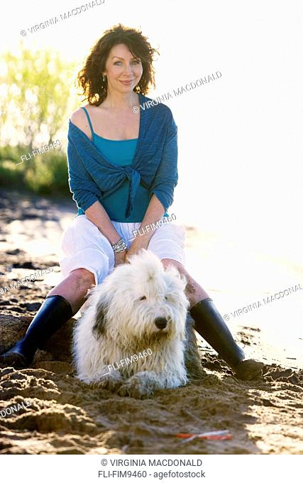 Portrait of a mature woman with a dog on a beach, Toronto, Ontario