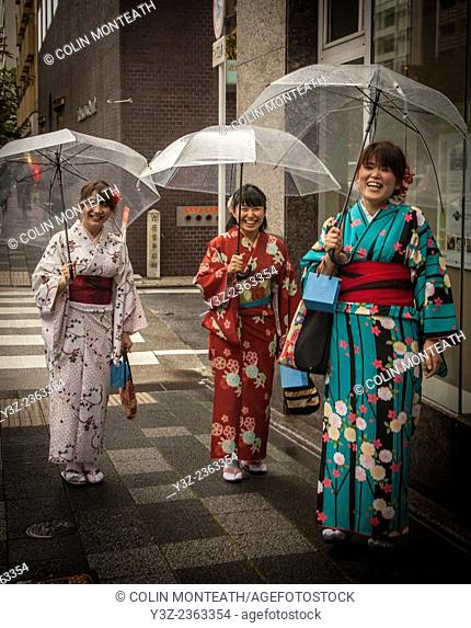 Three Japanese women in kimonos go shopping in the rain, Kyoto, Japan