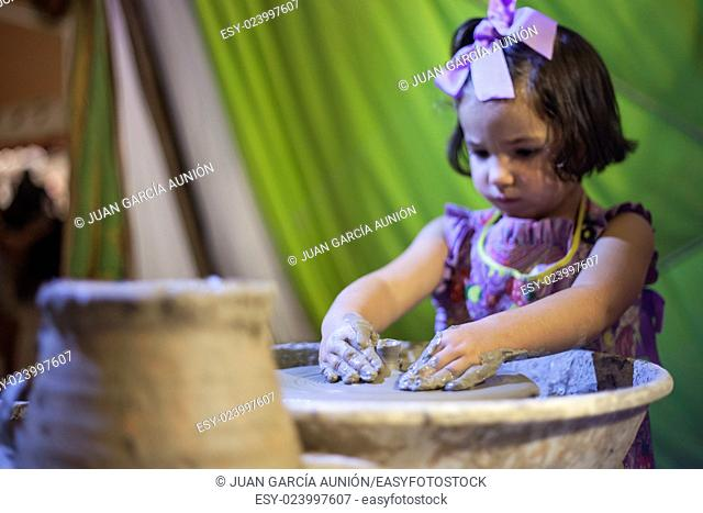 Little girl learning to work with potter's wheel. Selective focus