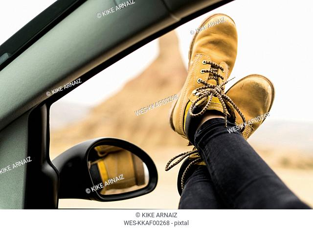 Spain, Navarra, Bardenas Reales, legs of young woman leaning out of car window