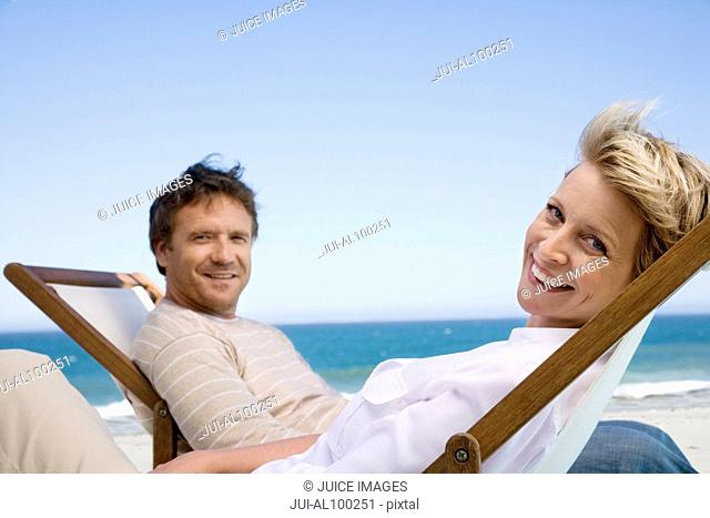 Couple in deck chairs near ocean