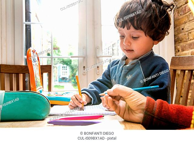 Mother and son writing in notebook