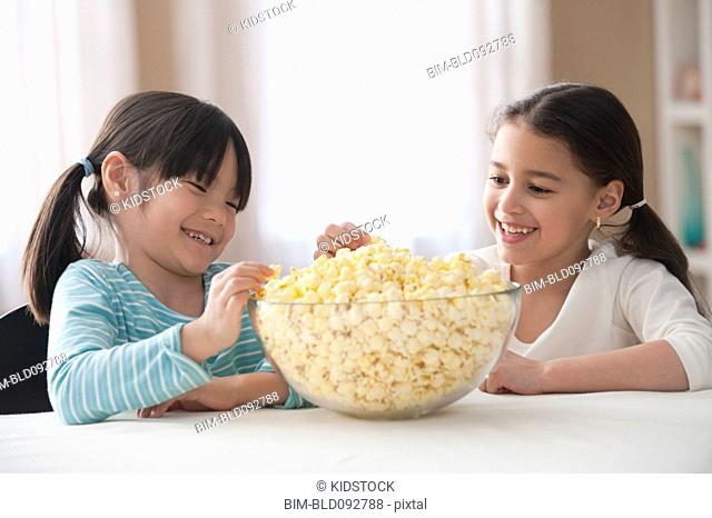 Hungry girls eating popcorn