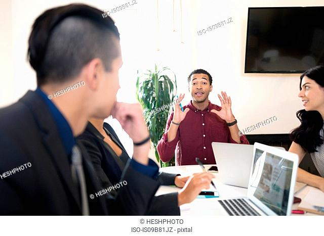 Young businessman explaining at boardroom table