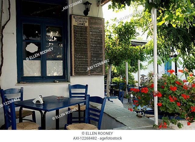 Traditional wooden chairs and red geraniums outside a taverna; Apollonia, Sifnos, Cyclades, Greek Islands, Greece