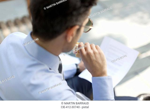 Corporate businessman eating lunch and reading paperwork