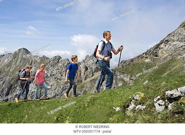 Father teenage kids hiking in mountains Alps