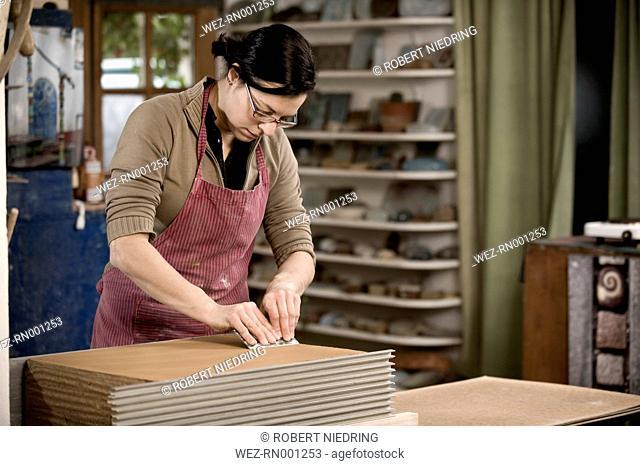 Germany, Bavaria, Mid adult woman preparing slices of clay in workshop