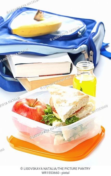 Lunch box with sandwich apple and milk