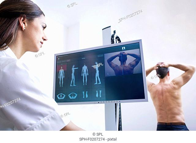 Doctor looking at monitor, examining male patient