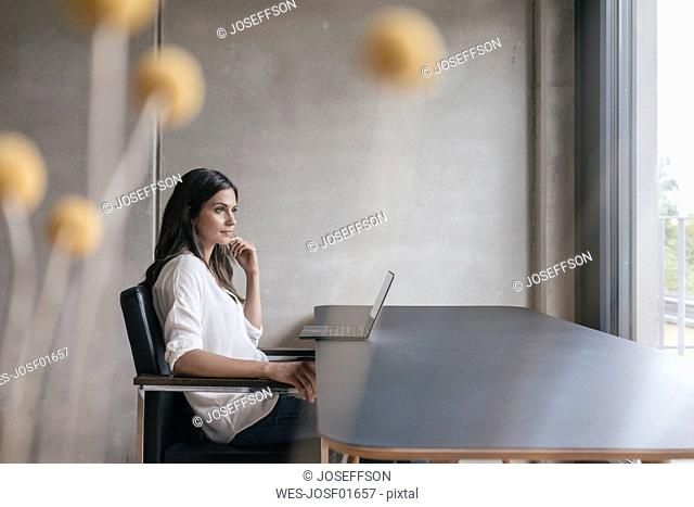 Thoughtful woman sitting at table with laptop
