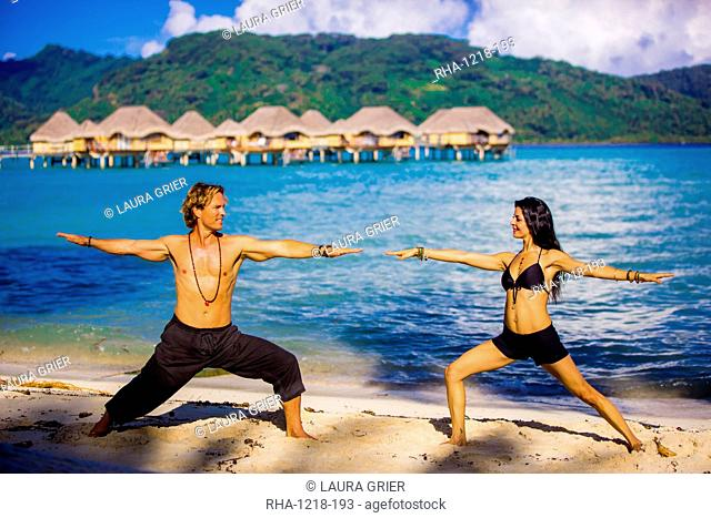 Couple doing yoga in front of overwater bungalows, Le Taha'a Resort, Tahiti, French Polynesia, South Pacific, Pacific