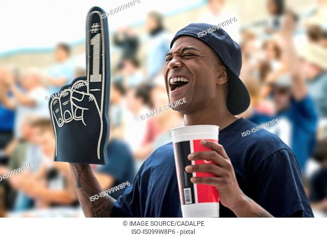 Man at sports game with foam hand and soft drink cup