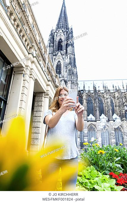 Germany, Cologne, young woman taking a selfie with smartphone in front of Cologne Cathedral