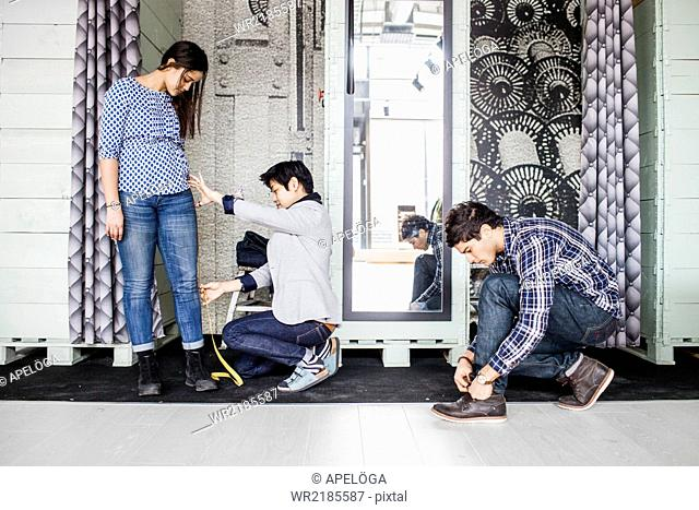Fashion designer taking measurement of female client while man tying shoe lace in jeans factory