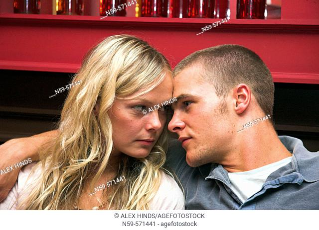 Attractive young couple cuddle up close in a bar