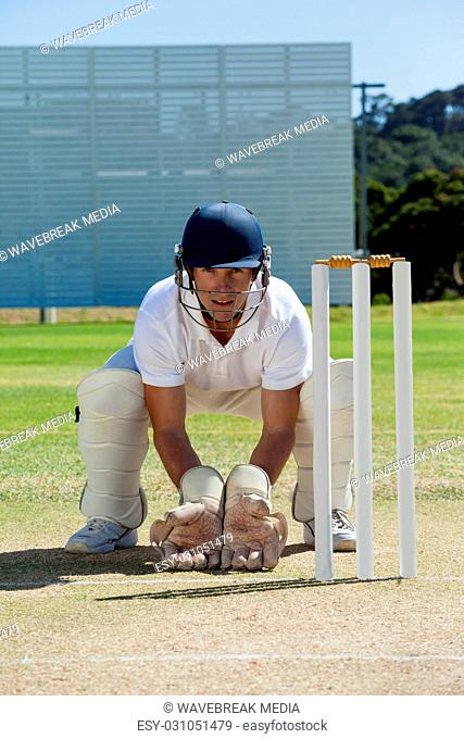 Portrait of wicketkeeper crouching behind stumps on field